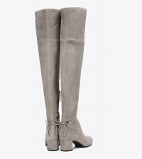 ihocon: TORY BURCH     DETAILS Lean, clean and elongating — dressed up or down. Our Laila Over-the-Knee Boot is a flexible, comfortable and flattering style done in rich stretch suede with a side zip that makes it easy to step into. It features a bow tie with logo-accented disks and a metal-plated block heel — a detail that flashes into focus as you walk.  1.77 (4.5 cm) block heel with interior metal plate Designed to hit mid thigh Stretch suede upper Leather ties at back with metal double-T logo tips Side zipper Leather lining Rubber outsole Style Number 41621 Boot Size Guide Tory Burch LAILA SUEDE OVER-THE-KNEE BOOT過膝靴